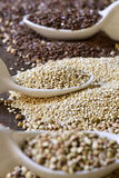 Seeds of buckwheat, quinoa and brown flax. Closeup of some ceramic spoons with different edible seeds on a rustic wooden surface, with the focus in the quinoa Stock Photo