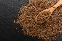 Seeds of cumin on a dark stone background.  Stock Image
