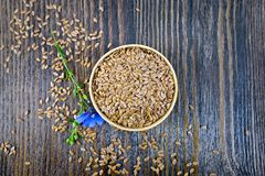 Flaxen brown seed in bowl with flower on board top. Seeds flaxen brown in a bowl, blue flax flower on a wooden board background from above Royalty Free Stock Photo