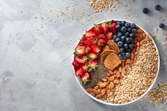 Fresh berries, almonds, oatmeal and granola in a plate with gray concrete background top view. Healthy food. Seeds of granola, oatmeal, ripe berries and nuts in Royalty Free Stock Photos