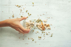 Seeds and nuts are scattering from the jar. Female hand is scattering Seeds and nuts from the jar Stock Photos