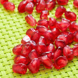 Seeds of pomegranate fruit. A pile of seeds of pomegranate fruit on a green woven background stock image