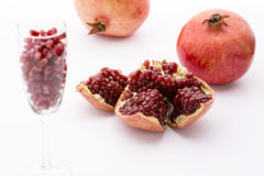 Seeds of the pomegranate, Punica granatum. A broken-up pomegranate with red, ripe seeds in its core. Pomegranate seeds in a champagne glass. Two whole fruits Royalty Free Stock Photos