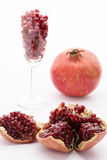 Seeds of the pomegranate. Ripe seeds of the pomegranate embedded in its white membrane. Purple pomegranate seeds in a champagne glass and an entire fruit, Punica Royalty Free Stock Images