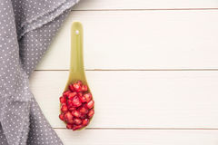 Seeds of red ripe peeled pomegranate on ceramic spoon. Stock Image