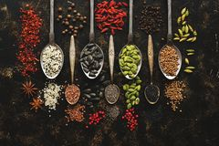 Seeds and spices in spoons on a dark background. View from above stock photography