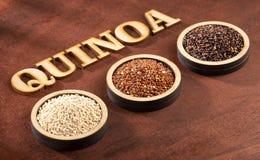 Seeds of white, red and black quinoa - Chenopodium quinoa. Wood background stock photo
