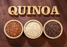 Seeds of white, red and black quinoa - Chenopodium quinoa. Wood background stock images