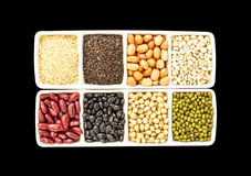 Seeds, whole grains in isolate on black. Millet, sesame, black sesame, peanuts, soybeans, red beans, green beans, black eyed peas (cereals) in the Cups.in Royalty Free Stock Images