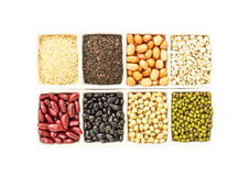 Seeds, whole grains in isolate on white. Millet, sesame, black sesame, peanuts, soybeans, red beans, green beans, black eyed peas (cereals) in the Cups.in Royalty Free Stock Photos