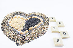 Seeds. Seeds written with chips with a heart made of seeds Stock Photos
