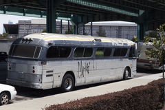 Seedy Converted Bus. Rear and side view of seedy, squalid, rundown former charter tour bus in shabby urban setting Stock Photos