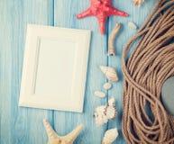 Seeferien mit leerem Fotorahmen, Sternfischen und Schiffstau Stockfotografie