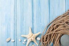 Seeferienhintergrund mit Sternfischen und -Schiffstau Lizenzfreie Stockfotos
