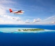 Seeflugzeugfliegen über kleiner Tropeninsel auf Malediven stockfoto