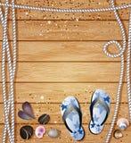 Seegrenze mit Flipflops, Kieseln, Seeoberteilen und Seilen auf einem Hintergrund von hölzernen Brettern mit copyspace für Ihren T Stockbild