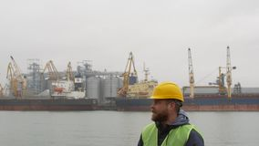 Seehafenarbeitskraft mit einem Bart und ein Sturzhelm auf dem Hintergrund von Schiffen stock video
