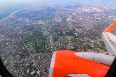 Seeing through airplane window and see overview city.Clouds in the sky and cityscapes though airplane window. stock image
