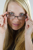 Seeing Better Soon. A pretty blond girl peers into the camera as she starts to put on her glasses Stock Photo