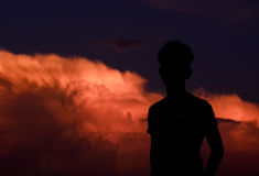 Seeing the cloud. A silhouette boy with cloudy background Royalty Free Stock Image