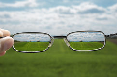 Seeing landscape through glasses. Out of focus nature with farmlands and a hand holding a glasses that correct the vision Royalty Free Stock Photography
