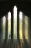 Seeing the light. Nature comes inside as the the Sun bursts through Rural Church's window and falls on cross royalty free stock images