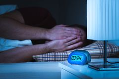 Seeing nightmares or bad dreams concept. Scared man covering face with hands in bed. Alarm clock on nightstand in bedroom stock images