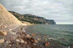 Seeküste am bewölkten Tag belichtet durch die Sonne Stockfotos
