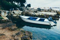 Seeküste, das adriatische Meer Ein hölzernes Fischerboot steht im Wasser auf einer steinigen Seemasse bei Ebbe nahe dem Ufer Lizenzfreies Stockbild