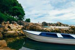 Seeküste, das adriatische Meer Ein hölzernes Fischerboot steht im Wasser auf einer steinigen Seemasse bei Ebbe nahe dem Ufer Stockbild