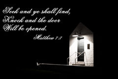 Seek And Ye Shall Find. Illuminated doorway surrounded by darkness with quote from the book of Matthew Stock Photos
