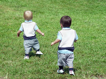 Seeking Adventure. Two twin toddler boys, identically dressed, running up a hill stock photo