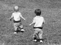 Seeking Adventure B&W. Two toddler twin boy, dressed identically, running up a grassy hill. This version is black and white stock image