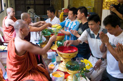Seeking Blessings. People seeking blessings from the monks in a Buddhist temple. Captured here are the activities in this process, namely the giving of money to royalty free stock photos