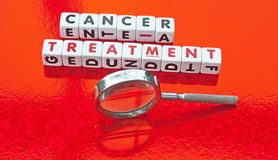 Seeking cancer treatment. Text 'cancer treatment' in uppercase letters inscribed on small white cubes with hand magnifier alongside, red background Stock Photography