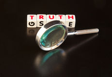 Seeking the truth. Text ' truth ' in red uppercase letters on small white cubes with a hand magnifier , dark background stock image
