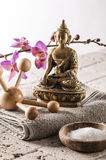 Seeking for wellbeing and energy with zen symbols. Spa and wellbeing concept - massage tool, Buddha and cup of bath salt with pink orchid flowers with natural Stock Image