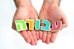Seeking work job and employment in Israel. Man hands hold the word WORK in Hebrew text (Avoda) isolated on white background multi purpose concept of Job hunting Royalty Free Stock Images