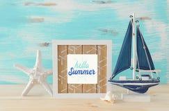 Seekonzept mit Fotorahmen und Segelboot ?ber Holztisch lizenzfreies stockbild