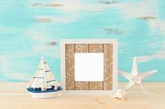 Seekonzept mit leerem Fotorahmen und Segelboot ?ber Holztisch F?r Fotografiemontage stockfotografie