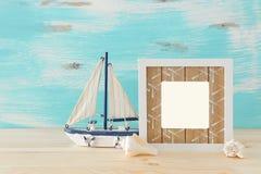 Seekonzept mit leerem Fotorahmen und Segelboot ?ber Holztisch F?r Fotografiemontage stockbild