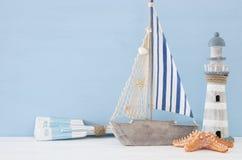 Seekonzept mit weißem dekorativem Leuchtturm, hölzernen Rudern und Boot über blauem Hintergrund stockfotografie