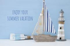 Seekonzept mit weißem dekorativem Leuchtturm, hölzernen Rudern und Boot über blauem Hintergrund lizenzfreie stockfotos