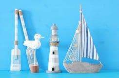 Seekonzept mit weißem dekorativem Seemöwenvogel, den lighthous, hölzernen Rudern und den Bootsrudern über blauem Hintergrund lizenzfreie stockbilder