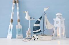 Seekonzept mit weißem dekorativem Seemöwenvogel, lighthous Laterne, hölzernen Rudern und Boot über blauem Hintergrund stockbilder