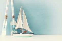 Seekonzept mit weißem dekorativem Segelboot und hölzernen Rudern über blauem Hintergrund stockfotografie