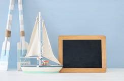 Seekonzept mit weißen dekorativen hölzernen Rudern und Boot nahe bei leerer Tafel über blauem Hintergrund stockbilder
