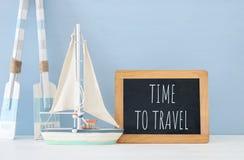 Seekonzept mit weißen dekorativen hölzernen Rudern und Boot nahe bei Tafel über blauem Hintergrund stockbilder