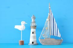 Seekonzept mit weißen dekorativen lighthous und des Bootes der Seemöwe Rudern des Vogels, über blauem Hintergrund stockfotos
