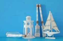 Seekonzept mit weißer dekorativer Leuchtturmlaterne, hölzernen Rudern, Buchstaben im Boot und Boot über blauem Hintergrund stockbilder